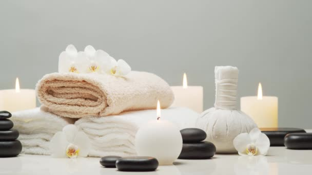 Spa background composition. Towel, candles, flowers, stones and herbal balls. Massage, oriental therapy, wellbeing and meditation concept.