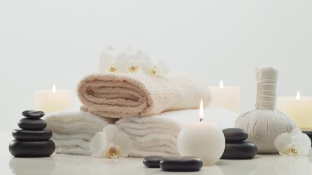 Keleti masszázs kezelés összetétele. Törölköző, gyertyák, virágok, kövek és gyógynövénygolyók. Spa eljárások, meditáció, jólét és aromaterápiás koncepció.