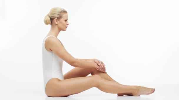 Fiatal, gyönyörű, fitt és természetes szőke nő fehér fürdőruhában, hidratáló krémet használva. Masszázs, bőrápolás, cellulitisz eltávolítás, sport és fogyás koncepció.