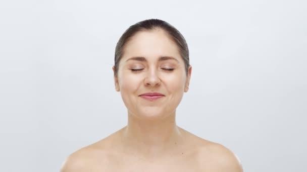 Studio portrét s úsměvem a šťastnou krásnou a přirozenou ženou. Zvedání obličeje, kosmetika a koncept make-upu.