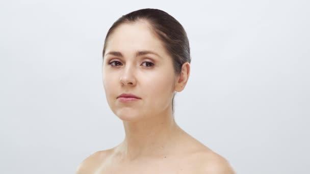 Studio portrét mladé, krásné a přirozené ženy. Zvedání obličeje, kosmetika a koncept make-upu.