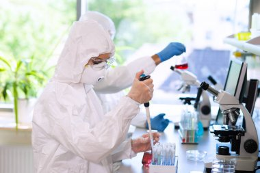Scientists in protection suits and masks working in research lab using laboratory equipment: microscopes, test tubes. Biological hazard, pharmaceutical discovery, bacteriology and virology concept.