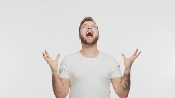Výrazný mladý muž křičící a křičící přes živé pozadí. Studio portrét pohledné osoby.