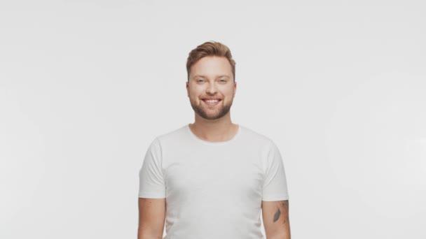 Výrazný a šťastný mladý muž přes živé pozadí. Studio portrét usmívajícího se pohledného člověka.