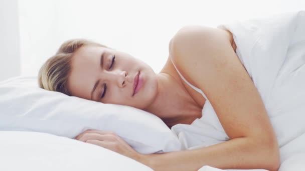 Mladá žena ležící v posteli. Krásná blonďatá spící dívka. Ráno v ložnici, denní světlo z okna. Koncept zdraví a odpočinku.