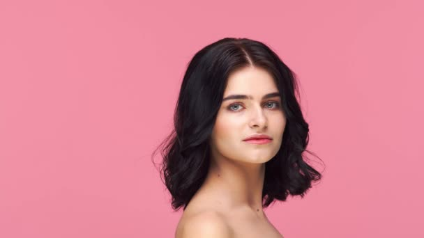 Studio portrét mladé a krásné brunetky žena přes růžové pozadí. Péče o pleť, zdraví, make-up a kosmetický koncept.
