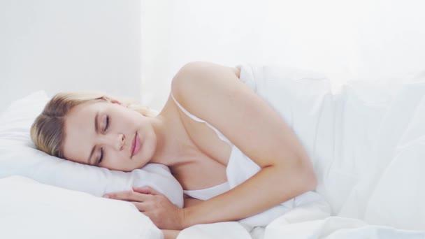 Egy fiatal nő fekszik az ágyban. Gyönyörű szőke alvó lány. Reggel a hálószobában, nappal az ablakból. Egészség és pihenés.