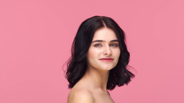 Studio portrait of young and beautiful brunette woman over pink background. Skin care, health, makeup and cosmetics concept.