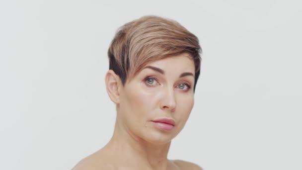 Közelkép egy középkorú érett nőről fehér agglegény felett. Egy érett hölgy portréja. Plasztikai sebészet, kozmetikai injekciók, kozmetikai koncepció.