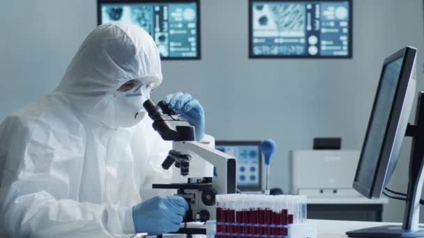 Scientist in protection suit and masks working in research lab using laboratory equipment: microscopes, test tubes. Coronavirus 2019-ncov hazard, pharmaceutical discovery, bacteriology and virology