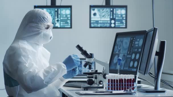 Wissenschaftler in Schutzanzügen und Masken arbeiten im Forschungslabor mit Laborausrüstung: Mikroskope, Reagenzgläser. Coronavirus covid-19 Hazard, pharmazeutische Entdeckung, Bakteriologie und Virologie