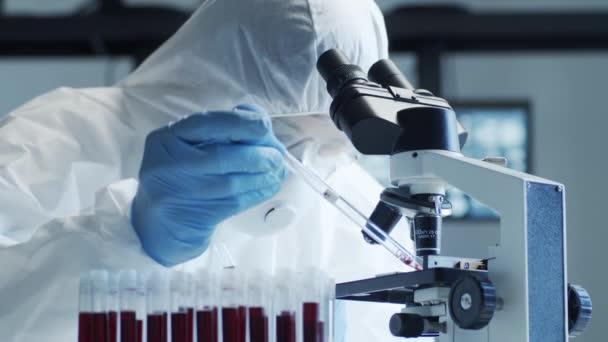 Vědec v ochranných oblecích a maskách pracující ve výzkumné laboratoři pomocí laboratorního vybavení: mikroskopy, zkumavky. Coronavirus 2019-ncov hazard, objev léčiv, bakteriologie a virologie