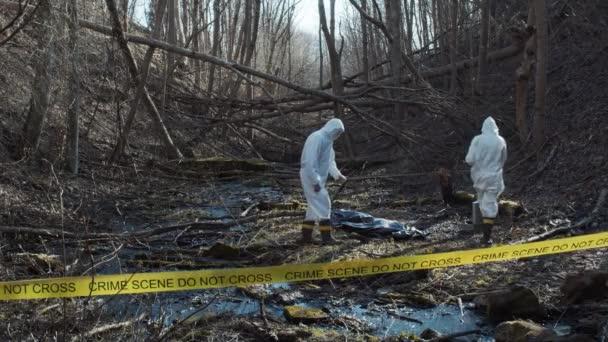Forenzní specialista pracující v lese. Policejní kriminalisté shromažďují důkazy a provádějí trestní vyšetřování. Koncept místa činu.