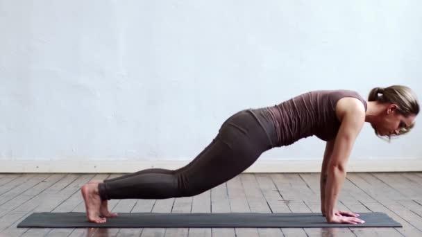 Mladá a zdravá žena cvičí jógu ve třídě. Protahování za denního světla. Sportovní, fitness, zdravotní péče a koncepce životního stylu.