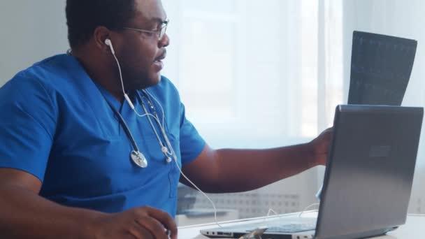 Professioneller afrikanisch-amerikanischer Arzt, der im Krankenhausbüro mit Computertechnologie arbeitet. Online-Beratung, Medizin und Gesundheitskonzept.