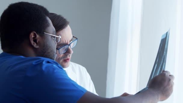 Az orvos és a sebész az ablak közelében beszélget, röntgent néznek. Orvosi dolgozók a kórházban. Nappali fény. Egészségügy, orvostudomány, csapatmunka koncepciók.