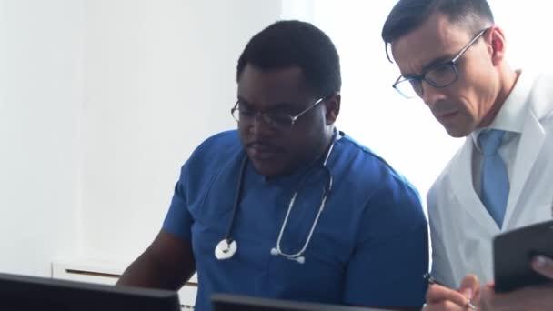 Arzt und Chirurg arbeiten im Krankenhausbüro mit Computertechnologie und Röntgen. Mediziner in der Klinik. Tageslicht. Gesundheitswesen, Medizin, Teamwork-Konzepte.