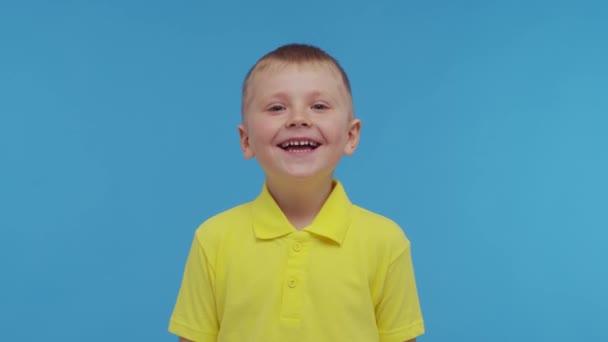 Egy boldog mosolygós fiú portréja pólóban. Vonzó és kifejező srác a stúdióban. A gyermekkor fogalma.