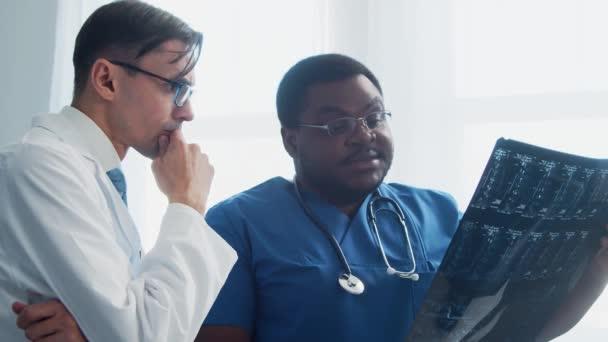 Arzt und Chirurg sprechen am Fenster und betrachten das Röntgenbild. Medizinisches Personal im Krankenhaus. Tageslicht. Gesundheitswesen, Medizin, Teamwork-Konzepte.