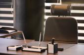 Pracoviště obchodní kanceláře. Sluneční svit v pracovním místě pro náčelníka, šéfa nebo jiné zaměstnance. Stůl a pohodlná židle. Procházejte polootevřenými žaluziemi