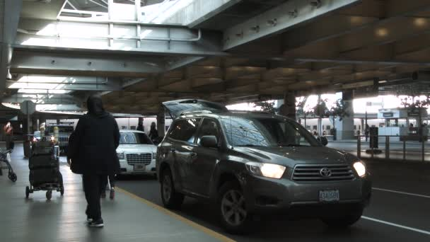 Exterior airport at baggage claim pick up area with people welcoming home their family members.