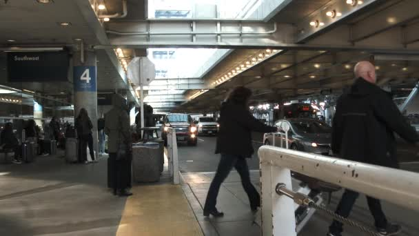 People leaving baggage claim at airport with traffic in line for pick up.