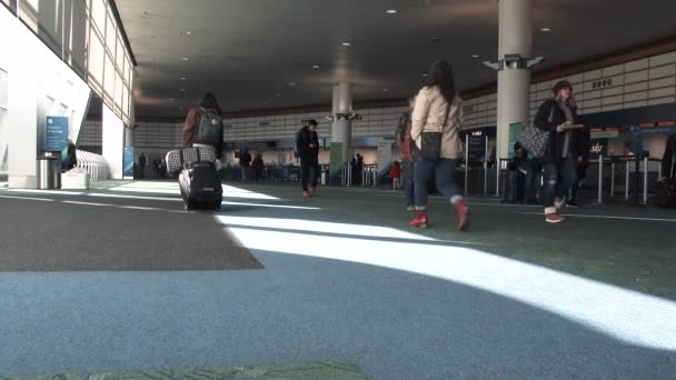 People traveling walk through airport by ticketing area.