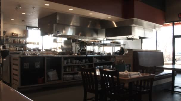 Timelapse and time delay effect inside restaurant at kitchen line with servers and wait staff taking orders.