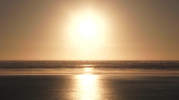 Vlny narážející na písečné pobřeží oceánu se sluncem soustředěným na klidný den.
