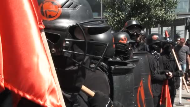 Members of the Antifa stand in in line ready for battle wearing helmets and holding shields.