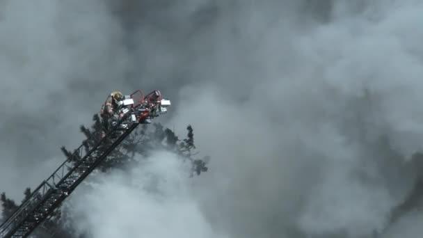 Hasič v plné rychlosti šplhá po žebříku ke sledování hořícího lesa.