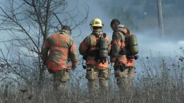 Firefighters make a plan and take action to contain large burning fire.