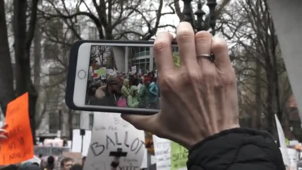 Person filming from her phone, March For Our Lives crowd protest gun violence.