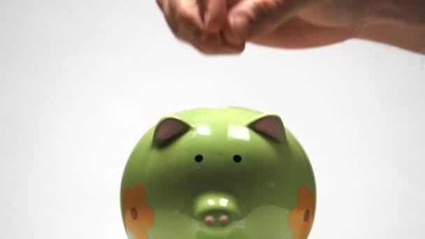 Ve studiu, ruka člověka přidá mince do prasátko banky a pak přidá dolarovou bankovku, aby to doplnil.