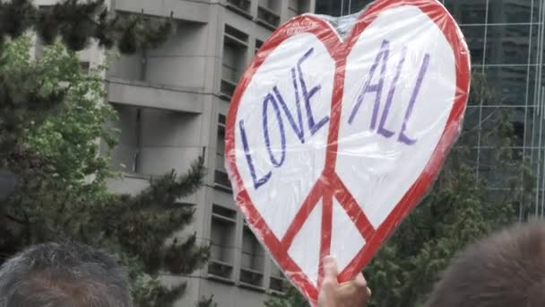 Person at rally holding a heart shaped peace sign reading Love All.