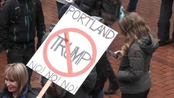 Woman holding a No Trump sign gathers with other protesters in downtown Portland on inauguration day.