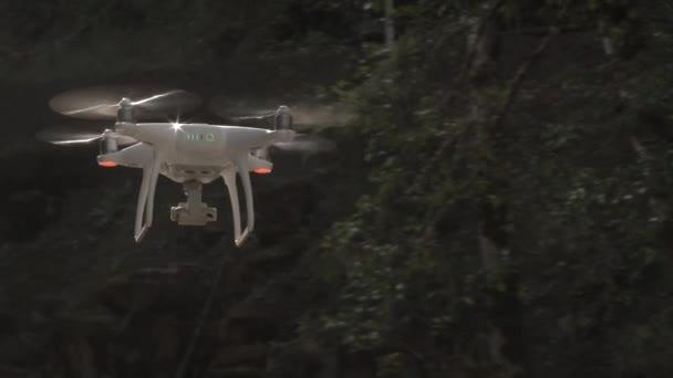 Quadcopter létání v různých letových drahách v lese.