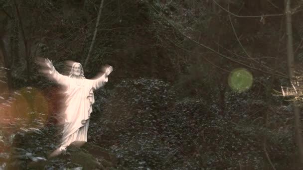 Kamera pánev a oddalovat od zářící sochy Ježíše Krista v lese Grotto na jasné, nebeské světlo zářící.