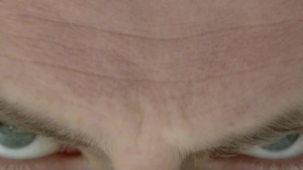 Zblízka zlověstně vyhlížející oči hledící do kamery.