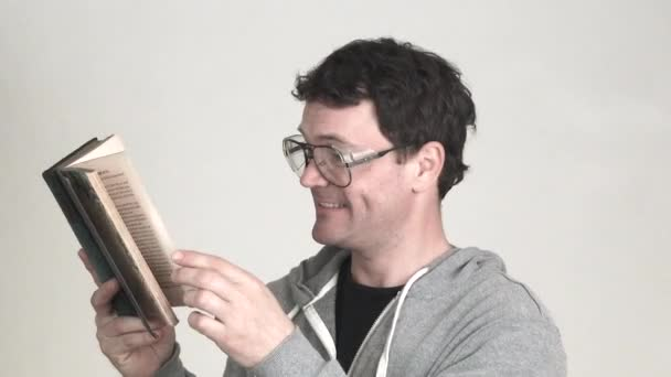 Model released man in studio wearing geeky glasses overly enjoys a classic book.