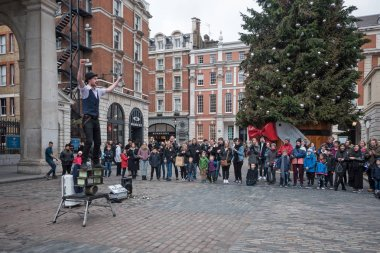 LONDON, UK - CIRCA JANUARY, 2018: Knife juggler in front of Covent Garden Market during Christmas time.