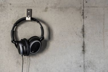 Headphones hanging on a concrete wall.