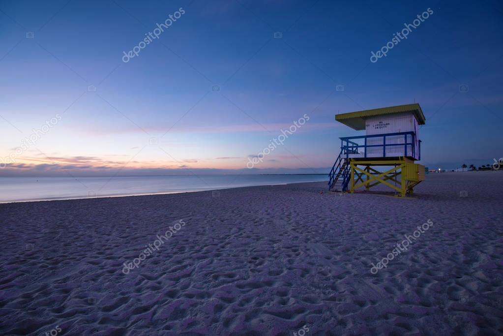 Lifeguard tower in a typical colorful Art Deco style at sunshine, with blue sky and Atlantic Ocean in the background. World famous travel location. Miami beach, Florida.