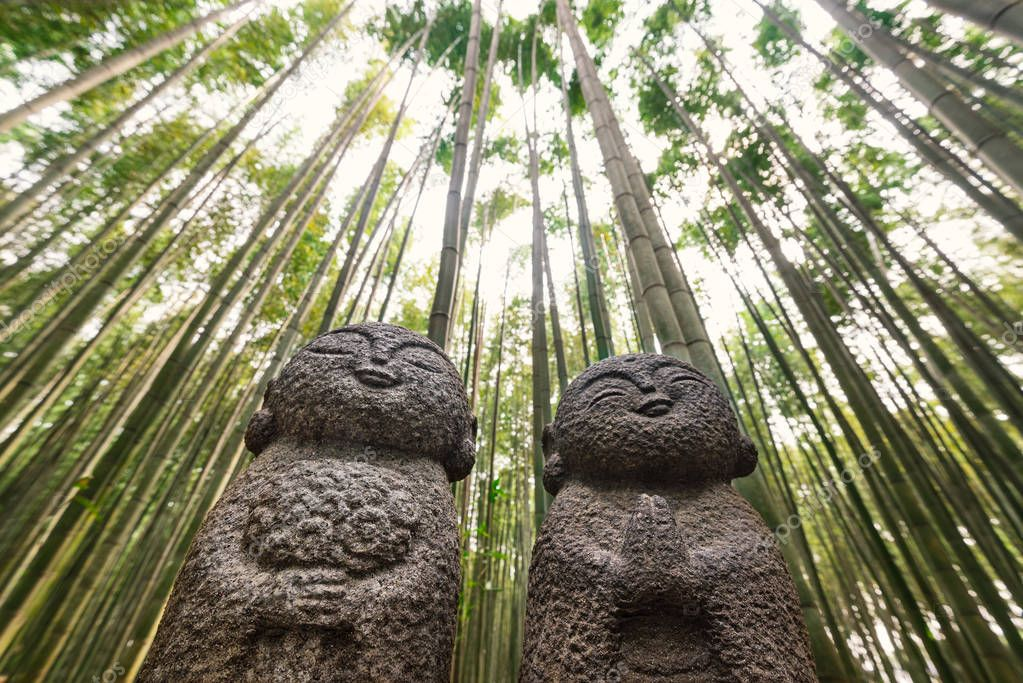 Jizo, Japanese stone statues with bamboo forest background. Kyoto, Japan.