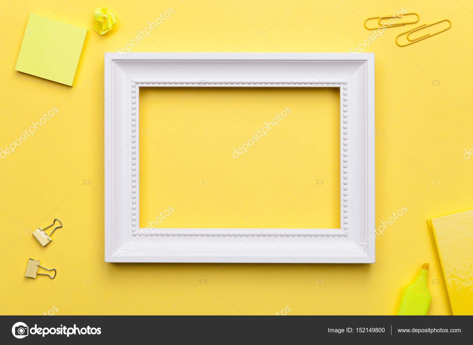 Cadre blanc avec des accessoires de bureau sur fond jaune