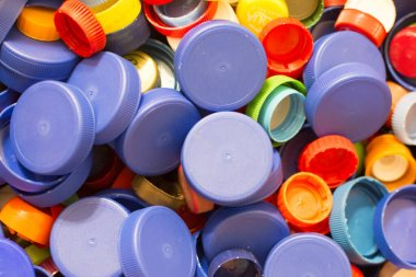 lot of multi-colored plastic bottle caps, close-up. Concept: waste disposal, environmental protection.