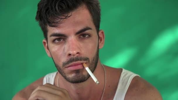 Hispán fiatalember dohányzás cigaretta, és a füstöt fúj