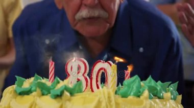 Cake And Senior Man Blowing Candles At Birthday Party