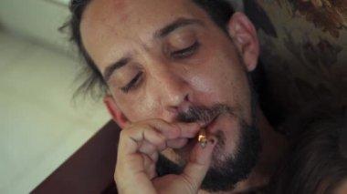 Young Man And Woman Smoking Marijuana Cigarette At Home