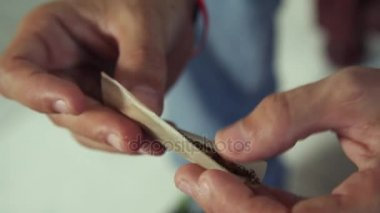 Man Preparing Hashish Joint Rolling Marijuana Cigarette For Smoking